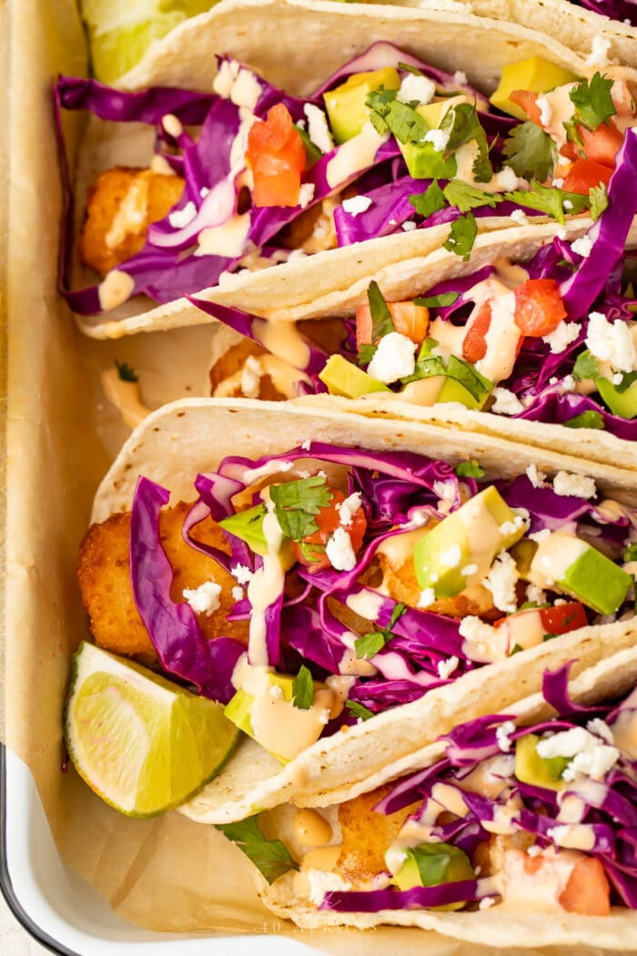 Close up view of fish stick tacos lined up in a baking dish