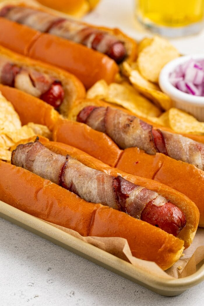 close up image of bacon wrapped hot dogs on a tray