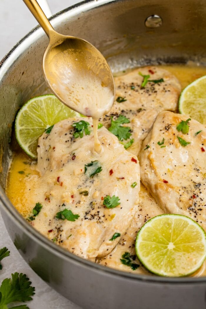 sauce being spooned over coconut chicken in a skillet
