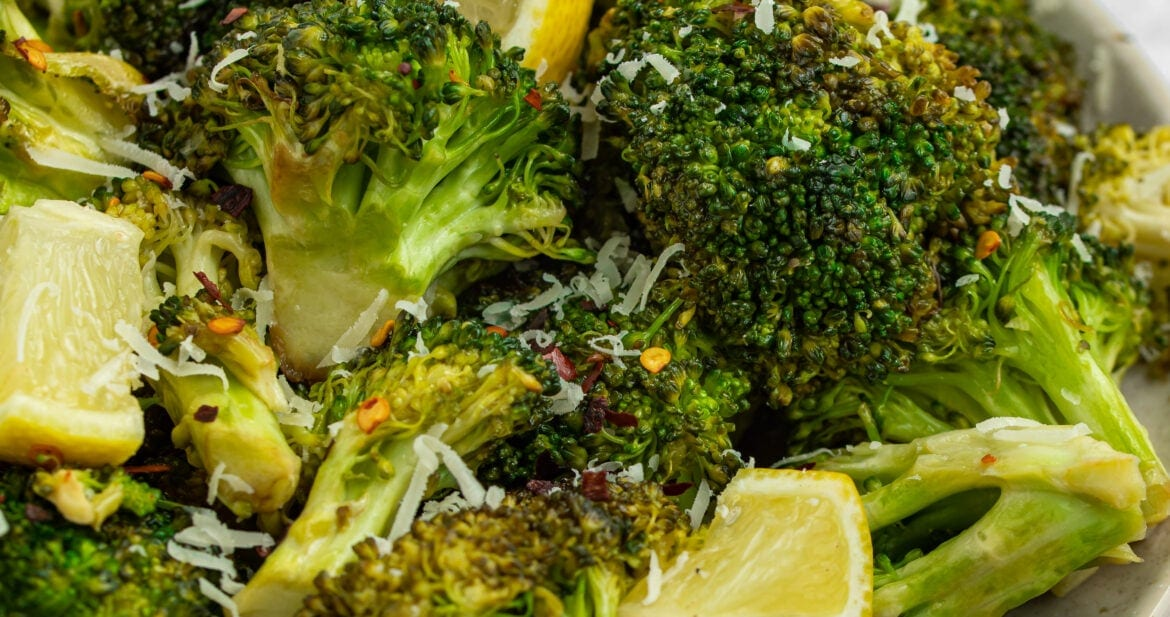 grilled broccoli on a plate with lemon slices and parmesan cheese on the side