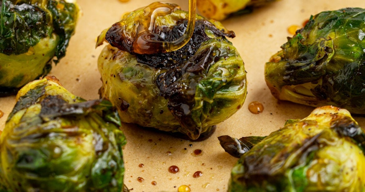 grilled brussels sprouts with honey being dripped over the top