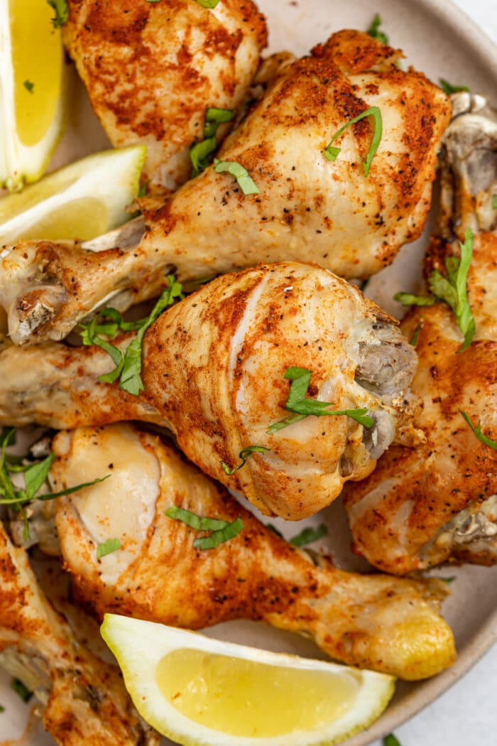 instant pot chicken legs on a plate with lemon slices