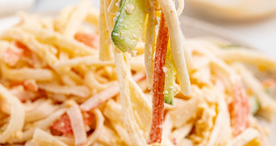 kani salad being lifted off a plate with chopsticks