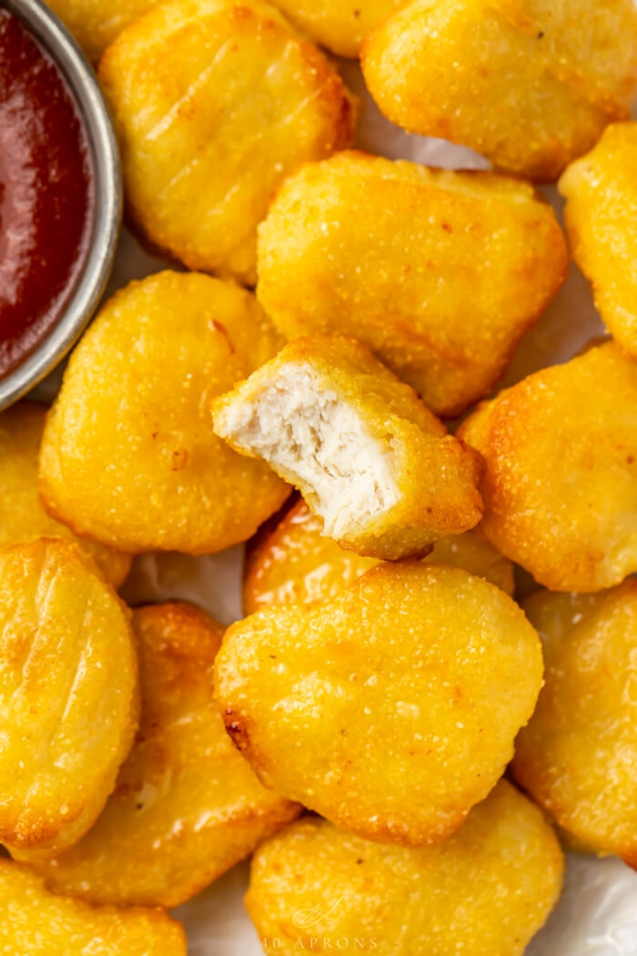 Close up of air fryer frozen chicken nuggets with one bite missing from a nugget