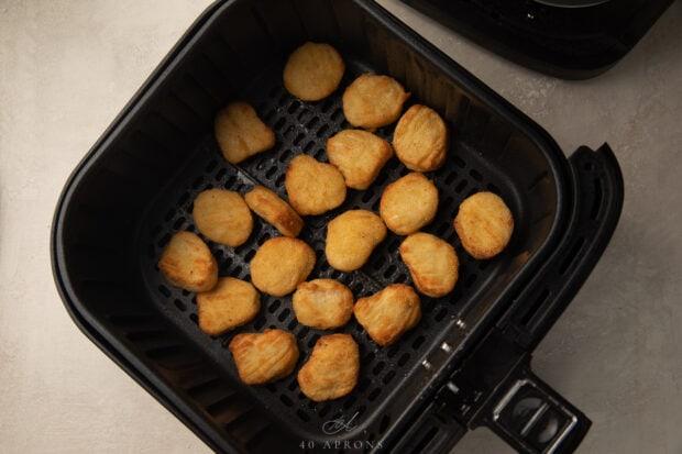 Frozen chicken nuggets in an air fryer basket