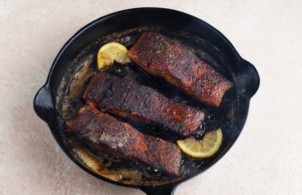 Blackened salmon filets in cast iron skillet