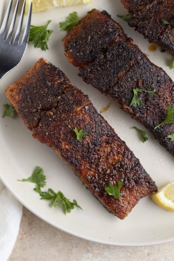 3 blackened salmon filets on a white plate with a lemon wedge