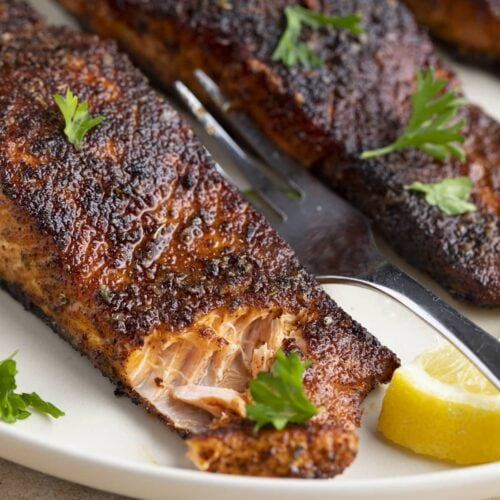 Angled view of blackened salmon on a white plate. The corner of the salmon has been cut into with a fork.