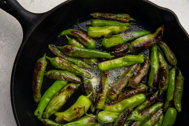 Shishito peppers in butter in a large cast iron skillet