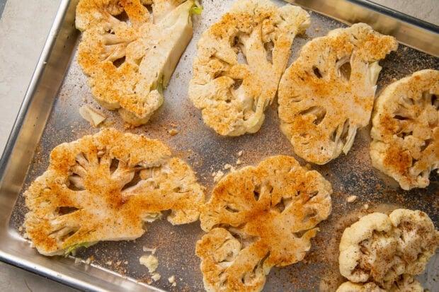 Seasoned cauliflower steaks on baking sheet