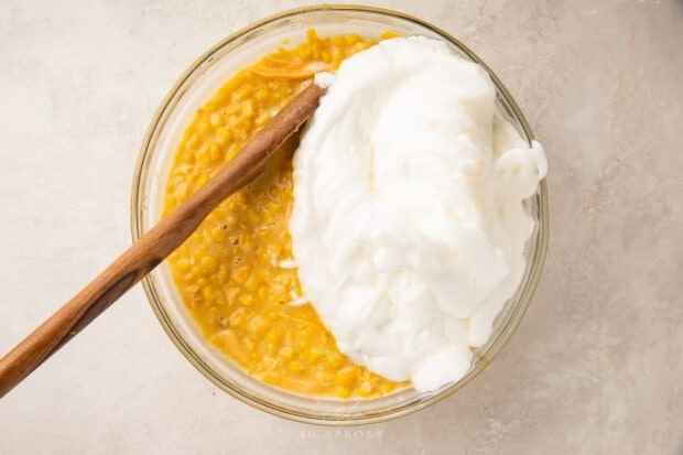 Mixture for corn souffle with whipped egg whites in a large glass bowl with a wooden spoon