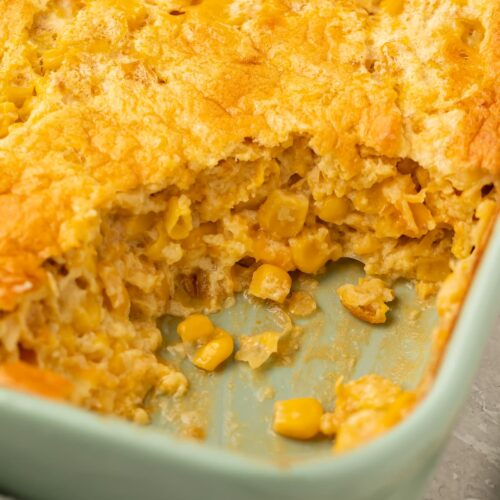 Angled photo of corn souffle with a scoop missing from the corner to show the inside of the souffle