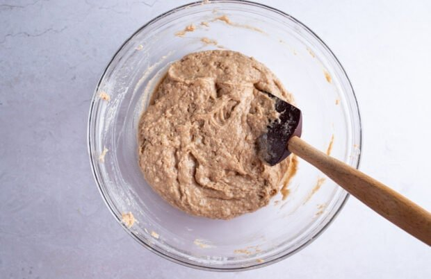 Gluten free zucchini bread batter in large glass bowl with silicone spatula