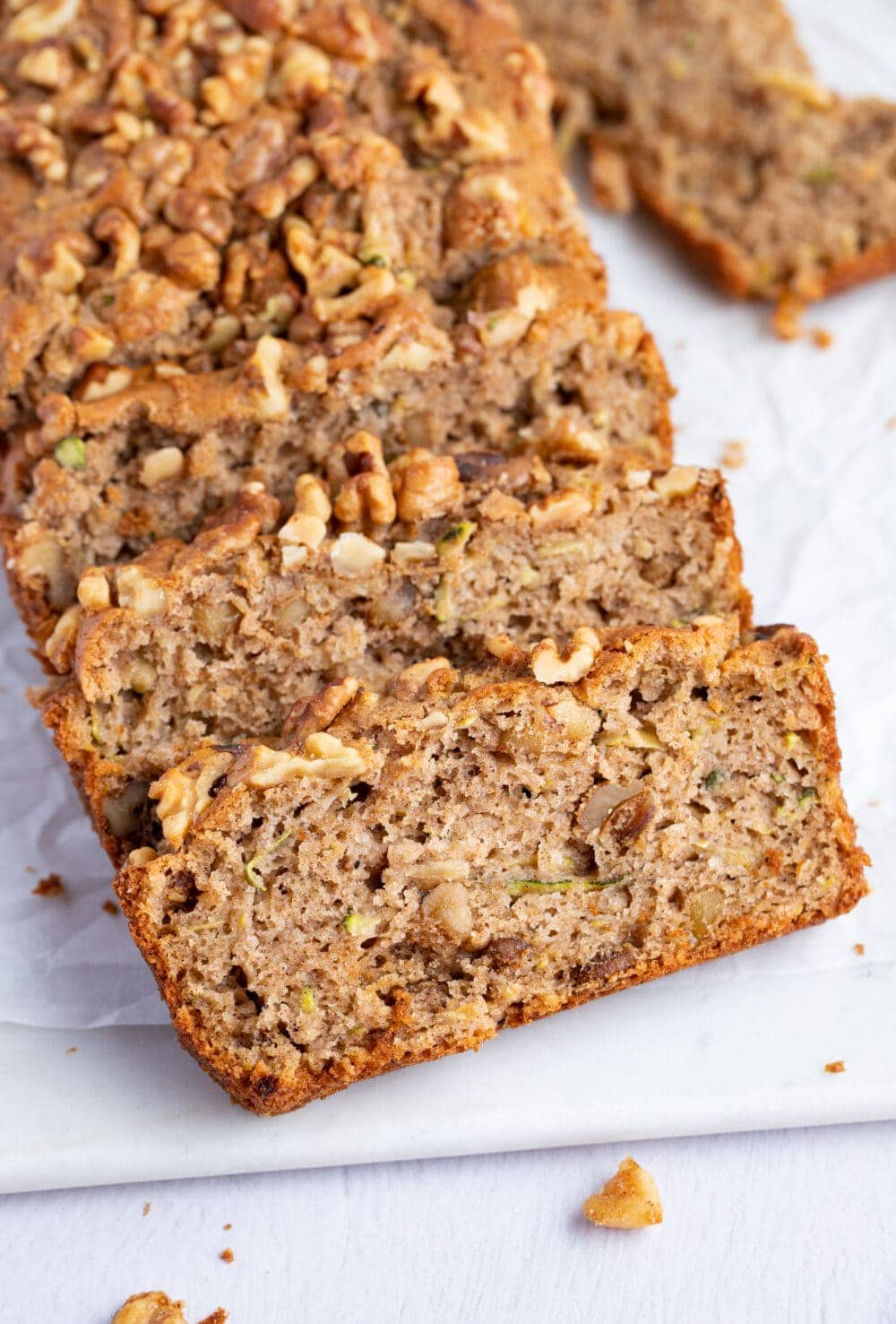 Slices of gluten free zucchini bread angled against each other on a white surface