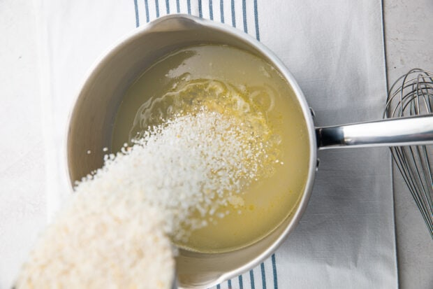 Pouring grits into saucepan
