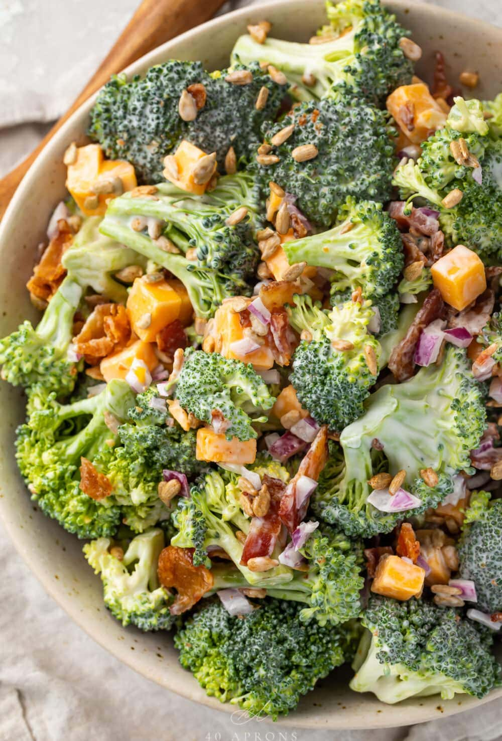 Keto broccoli salad in a large bowl on a table next to a wooden spoon