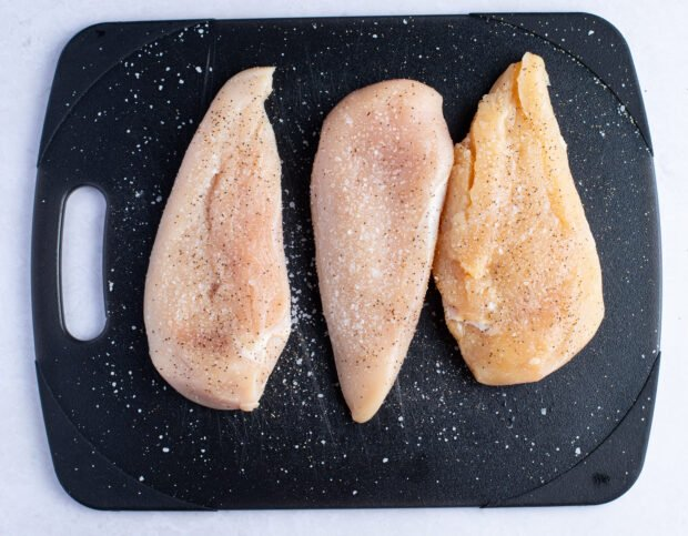 Chicken breasts seasoned with salt and pepper on cutting board