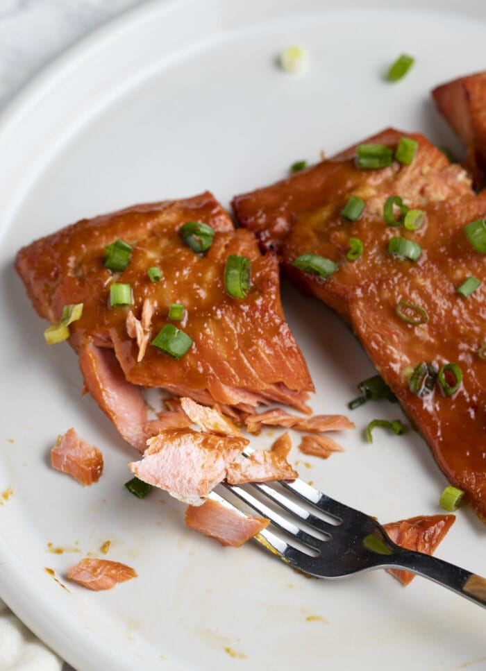 Miso salmon fillets on a white plate. The focus is on a fillet that has been cut with a fork to show the flaky interior meat