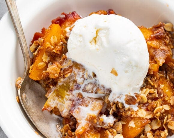 Peach crisp in a bowl topped with vanilla ice cream