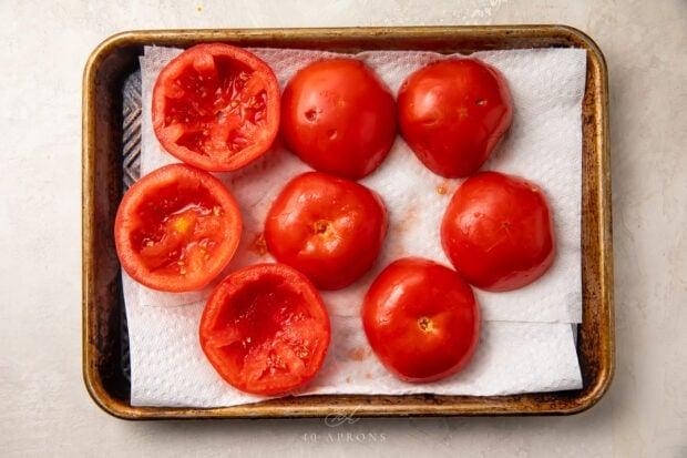 Halved tomatoes on baking sheet