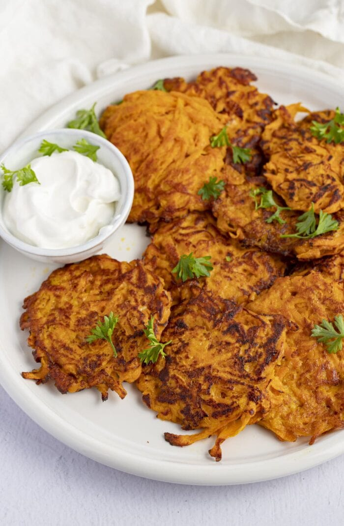 Sweet potato hash browns on a white plate next to sour cream