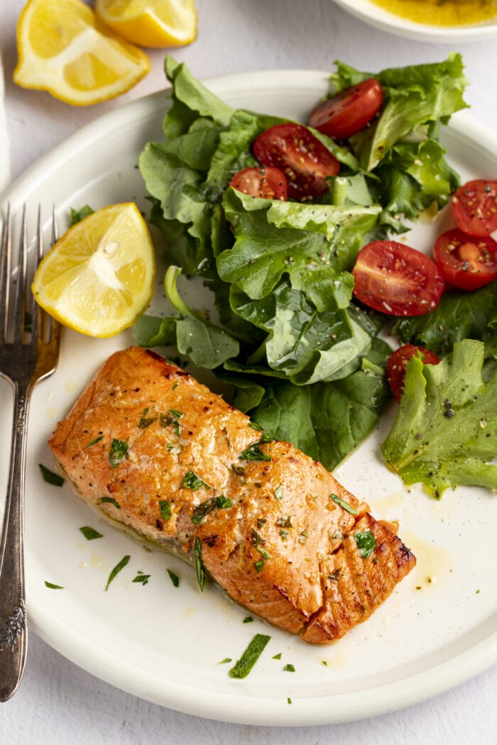 Broiled salmon on a plate next to a small salad and lemon wedges