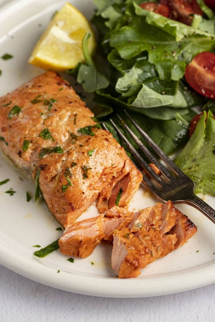 Broiled salmon on a plate next to a small salad