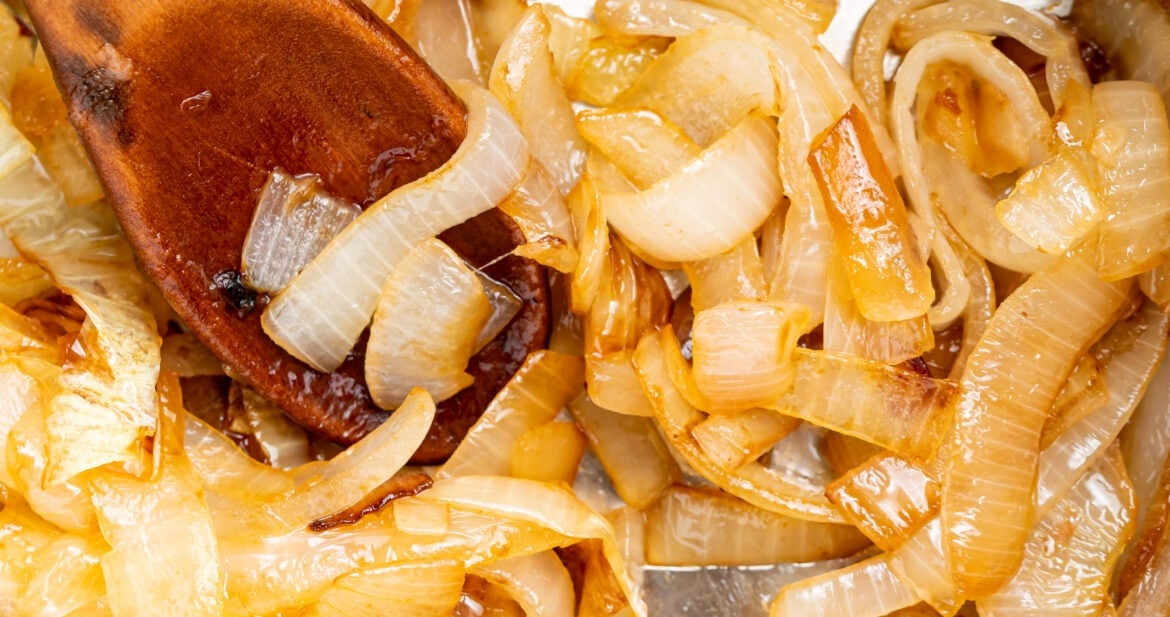 sauteed onions in a skillet with a wooden spoon