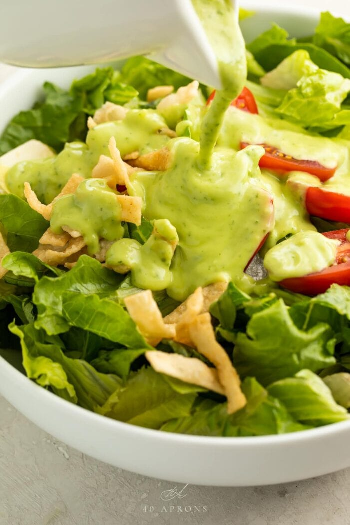 Avocado dressing poured over a salad in a bowl