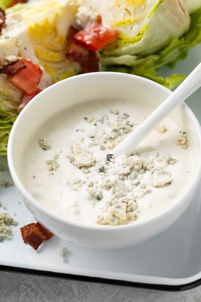 Blue cheese dressing in a small bowl next to salad