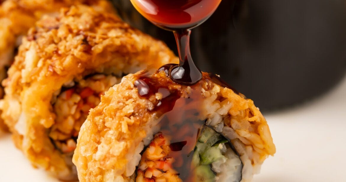 Eel sauce drizzled over pieces of sushi on a white plate