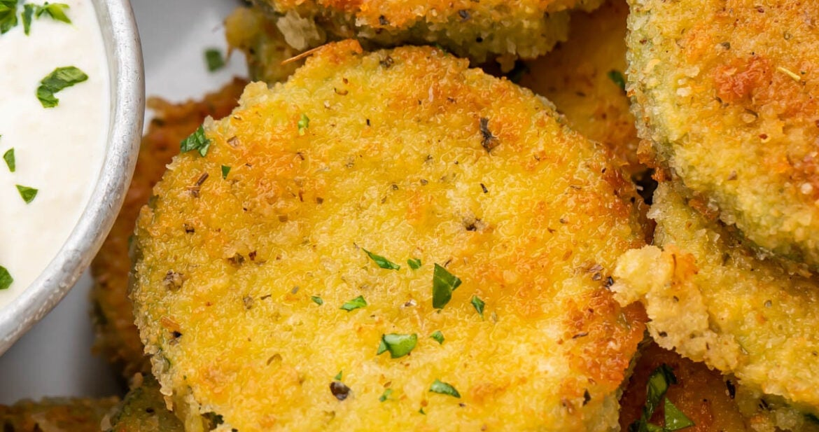 Crispy fried zucchini next to a creamy parmesan dipping sauce