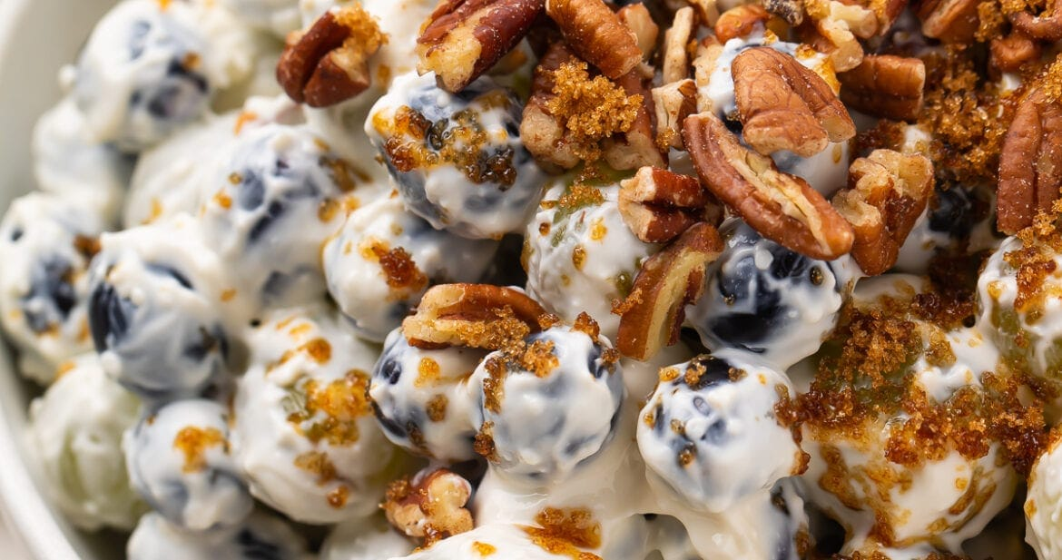 Creamy grape salad topped with pecans and brown sugar