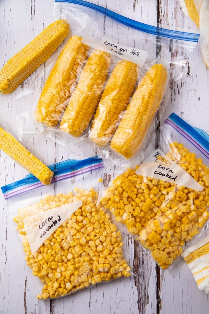 Corn cobs and corn kernels in freezer bags on a wooden table