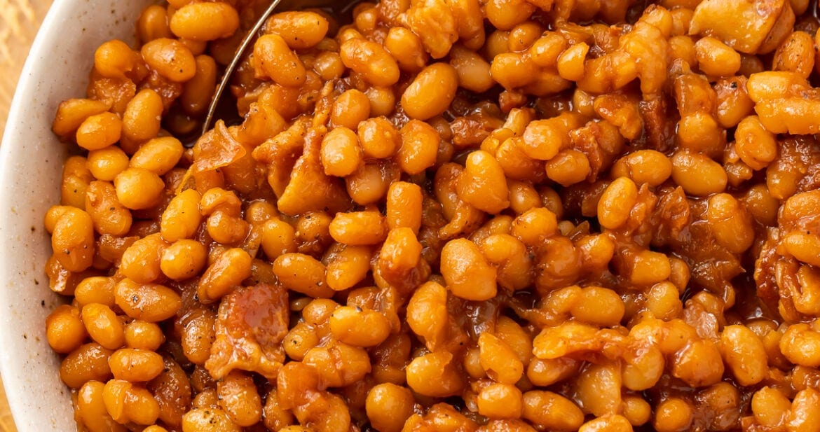 Overhead photo of Instant Pot baked beans in a white bowl on a wooden board