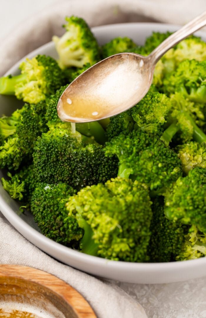 A spoon drizzles lemon butter sauce over Instant Pot broccoli in a large white bowl