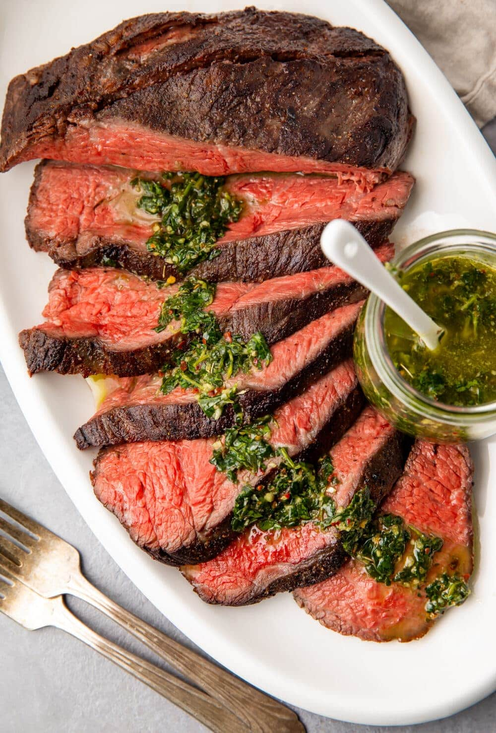 Sliced sous vide tri tip on a platter with chimichurri