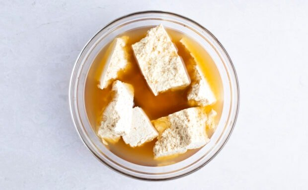 Tofu in glass bowl with vegetable broth