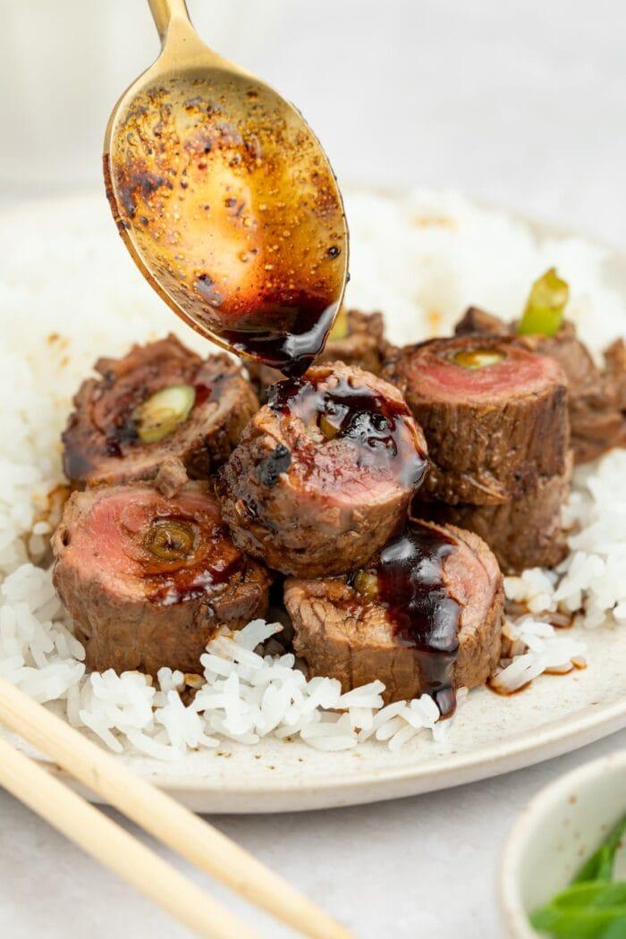sauce being spooned over beef negimaki rolls