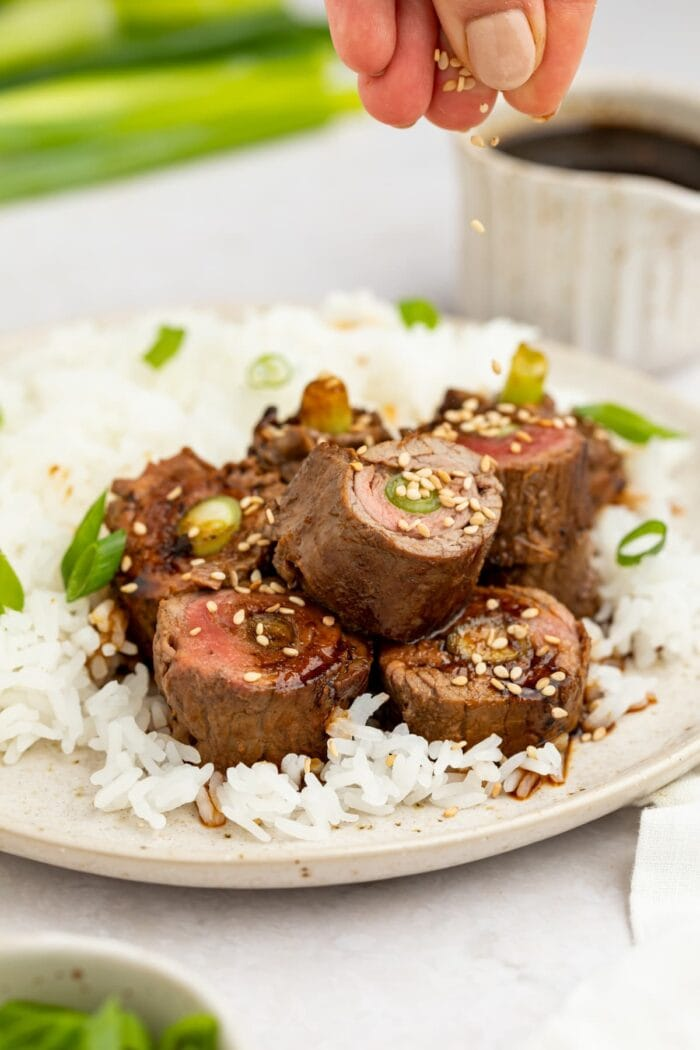 beef negimaki on a plate with rice and sesame seeds being sprinkled over the top