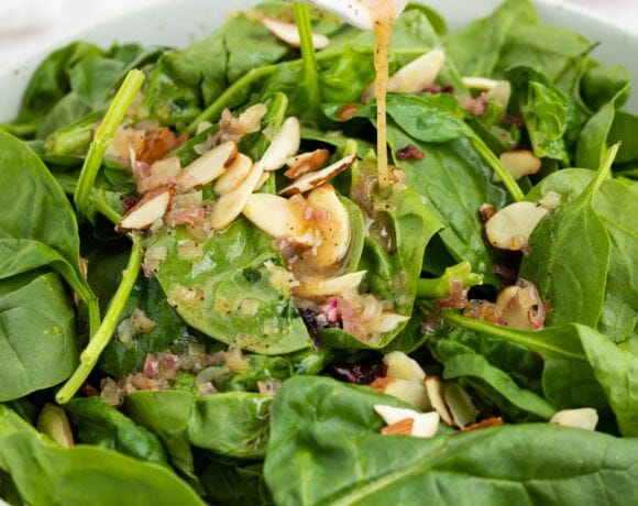 hot bacon dressing being poured over spinach salad