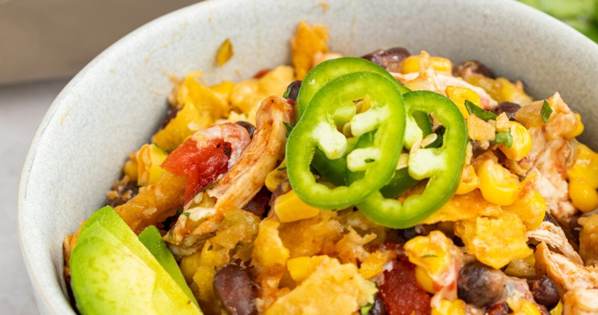 mexican chicken casserole in a bowl with sliced jalapenos and avocado on top