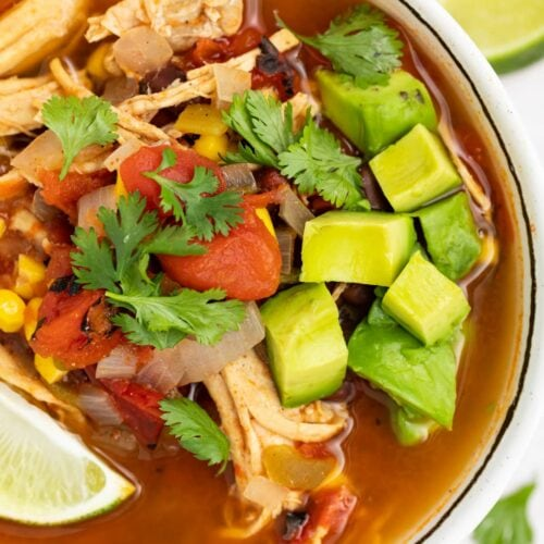 overhead image of mexican soup in a bowl with avocado, cilantro, and a lime wedge on top