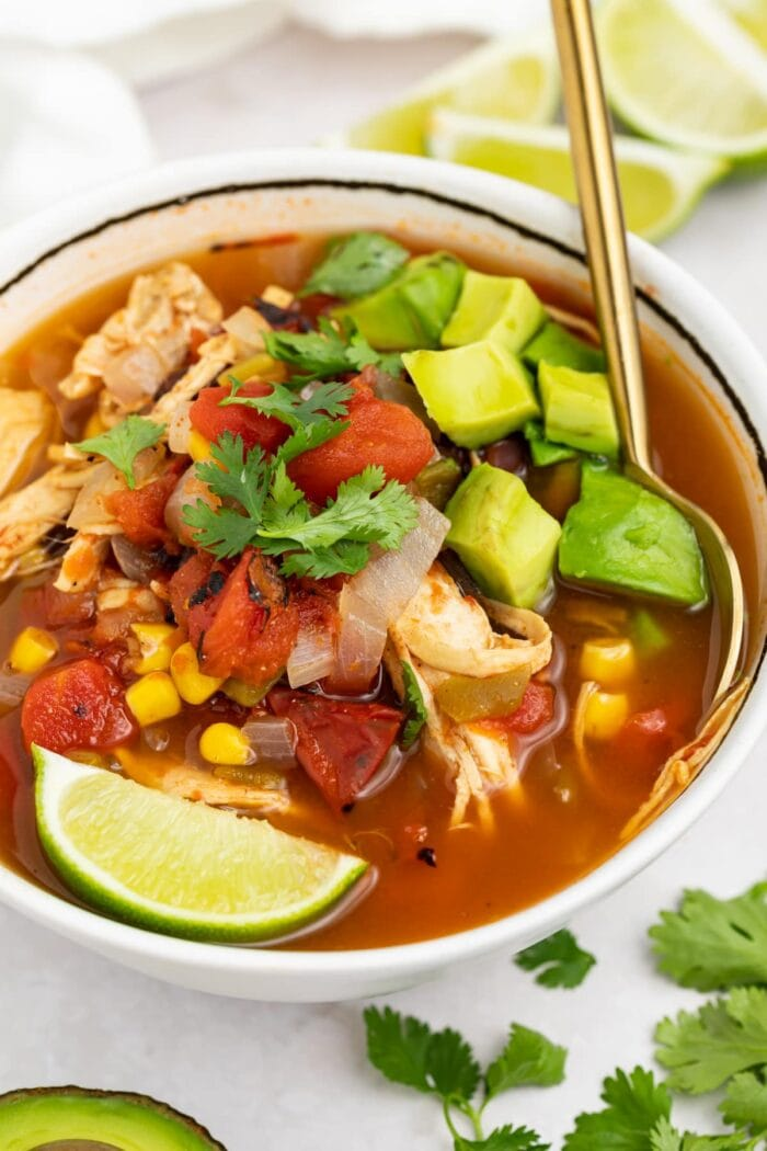 mexican soup in a bowl with a spoon and lime wedges, cilantro, and half an avocado on the side