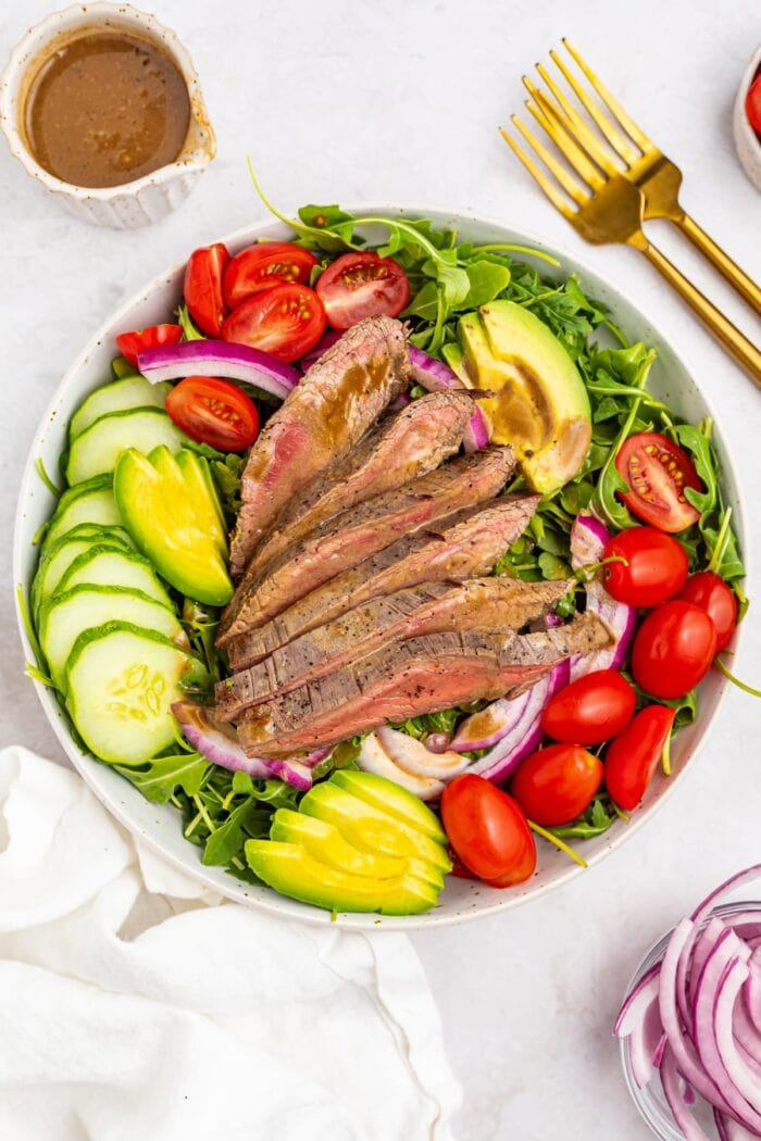 overhead image of steak salad with dressing, forks, and red onion on the side