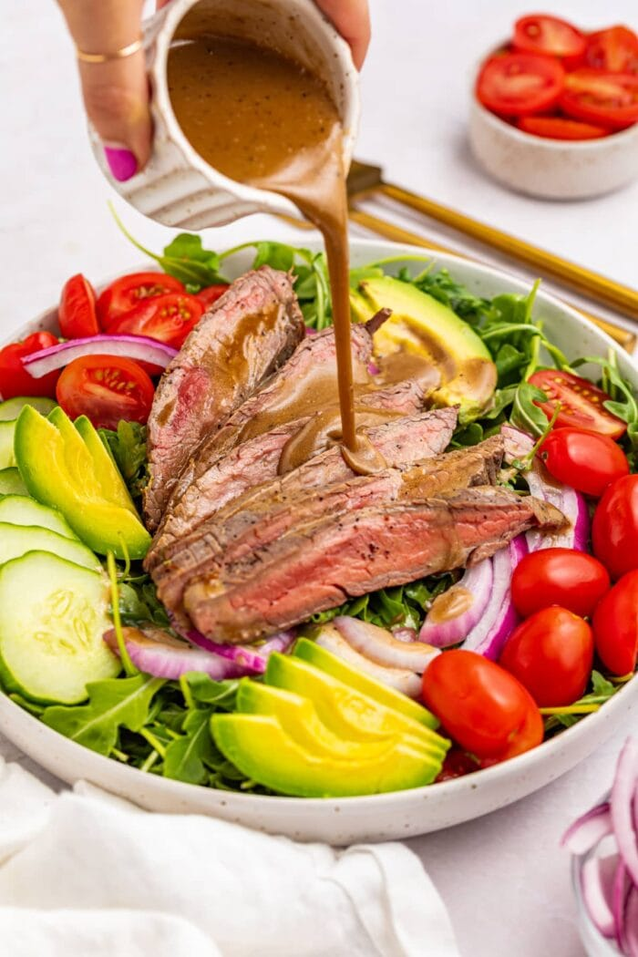 creamy balsamic dressing being poured over steak salad