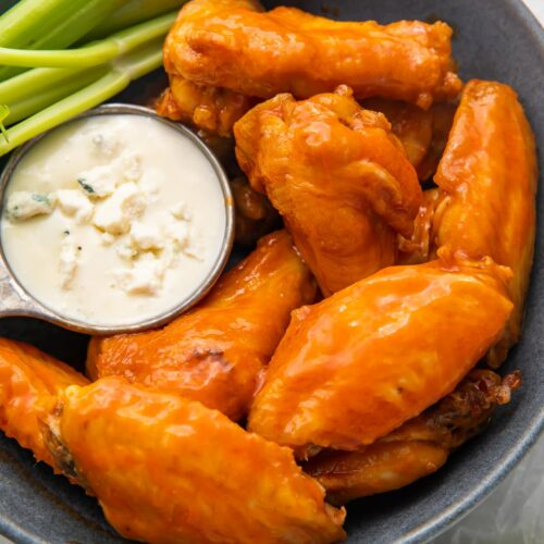 Air fryer chicken wings and celery on a platter with blue cheese dressing
