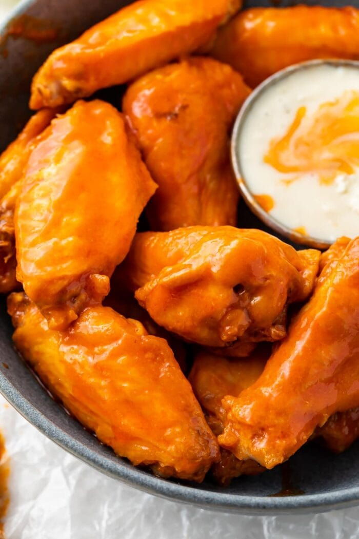 Air fryer chicken wings on a platter with sauce