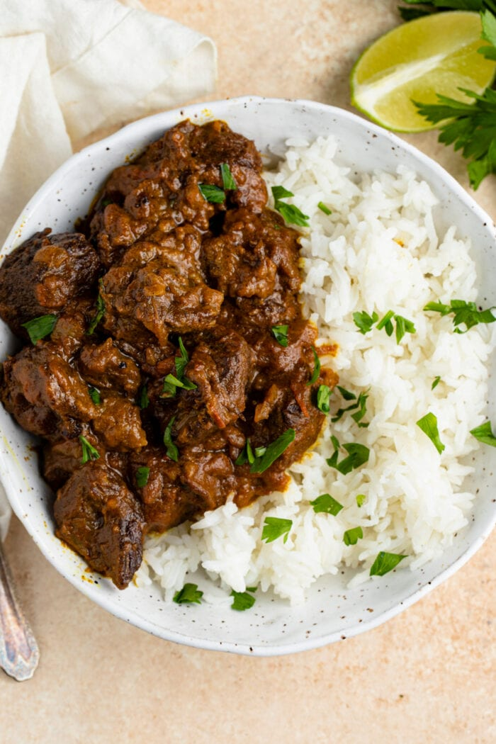 Overhead angle of beef curry with white rice in a bowl on a peach background