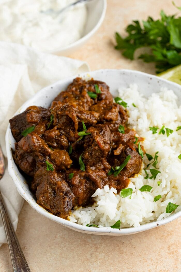 Beef curry in a white speckled bowl with white rice, garnished with parsley